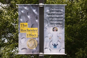 """Banner on light pole for """"The Rochester Effect"""" advertising campaign. OMEGA target bay in background. Reads: """"Delivering 40,000 joules per billionth of a second for energy ever better"""""""