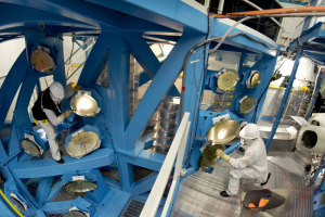Scott Hylas (left) and Mark Bowman (right) examine large UV-beam reflecting mirrors
